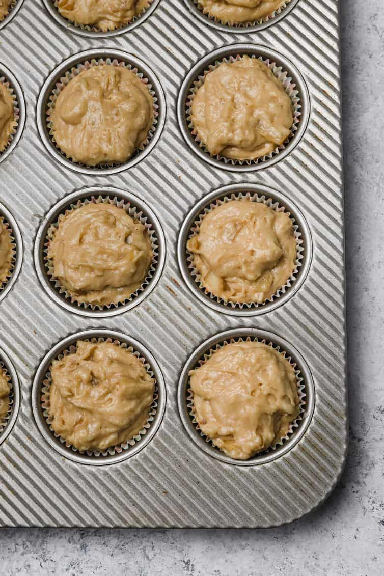 Apple muffin batter in muffin pan.