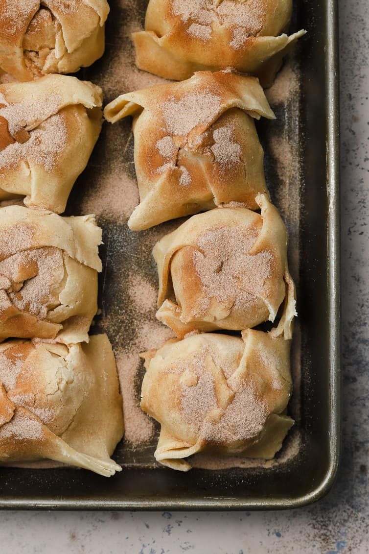 Prepared apple dumplings in a baking pan.