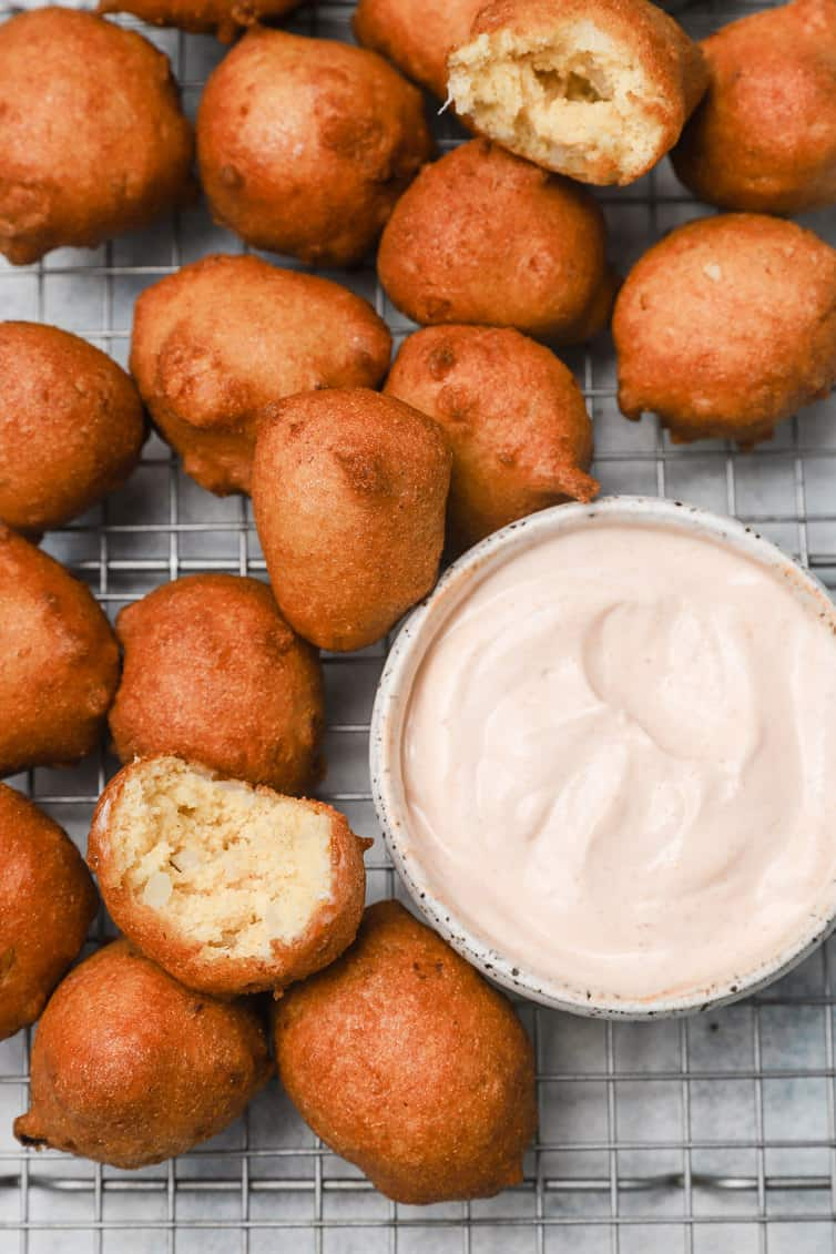 Hush puppies on wire rack with bowl of dipping sauce.