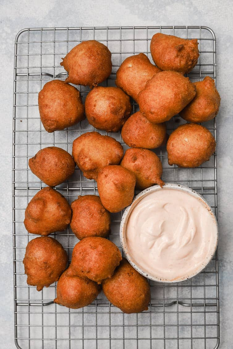 Hush puppies on cooling rack with bowl of dipping sauce.