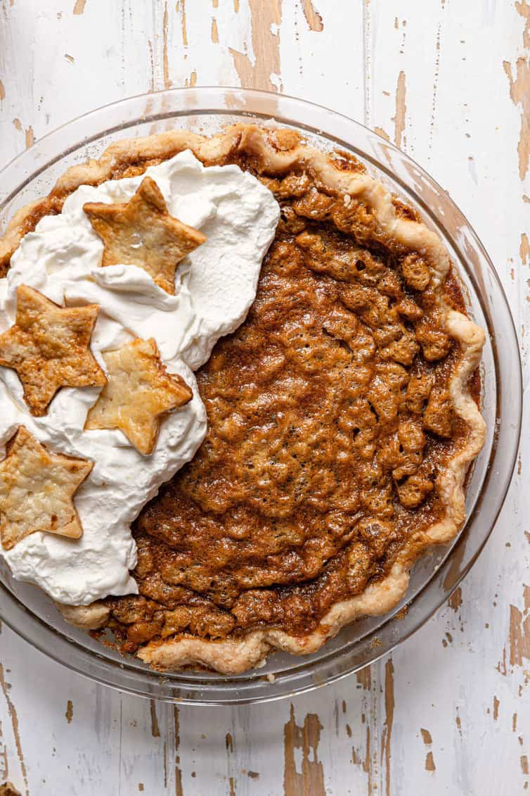 Chocolate walnut bourbon pie with whipped cream on half.