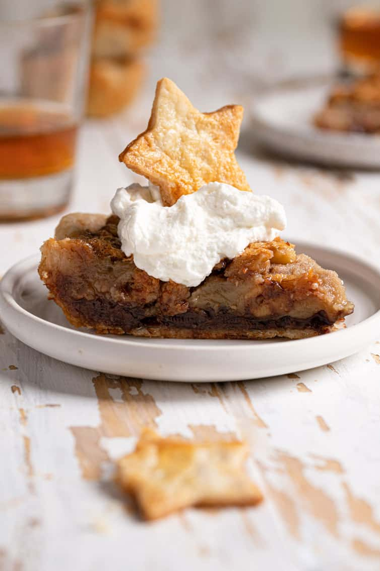 A slice of derby pie on a plate topped with whipped cream.