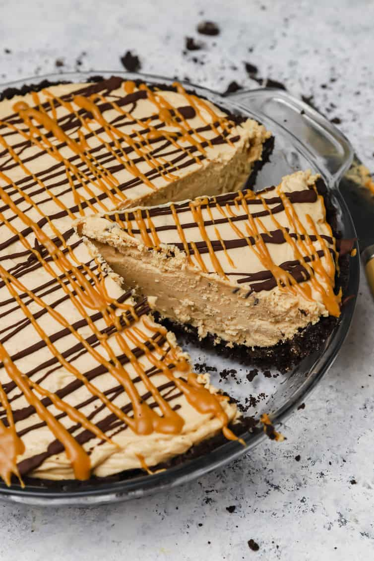 Peanut butter pie in a glass pie plate with a slice cut out.