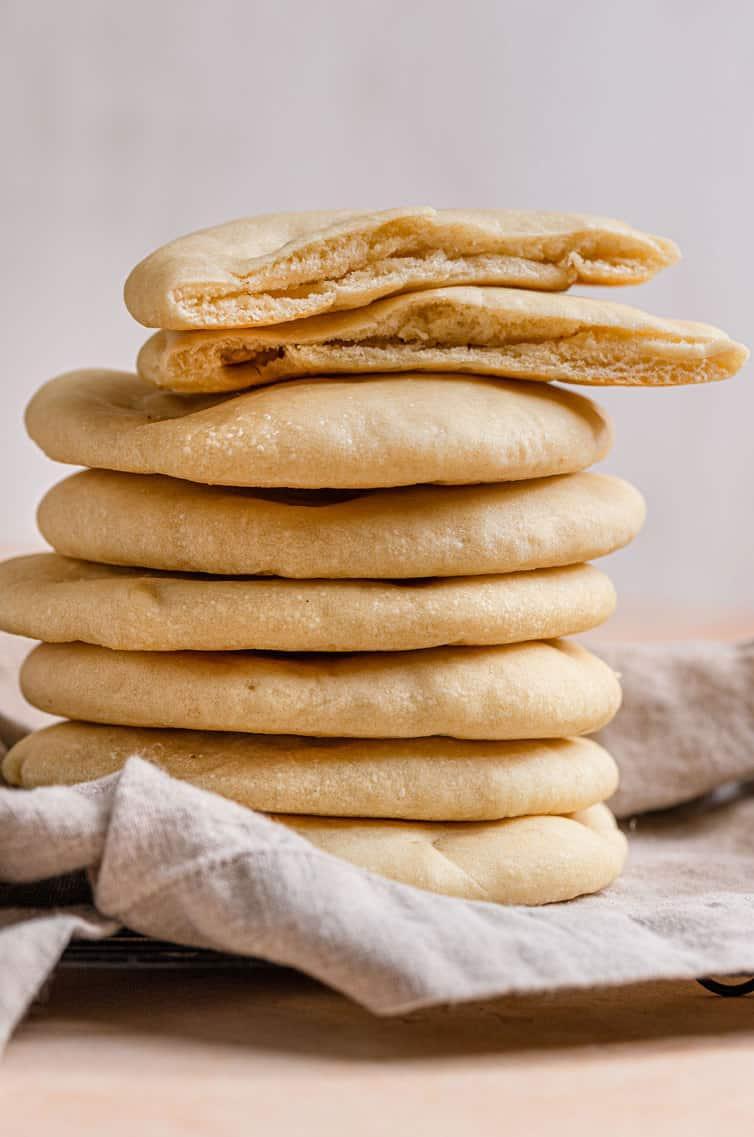 Uma pilha de pão pita com um corte ao meio no topo.