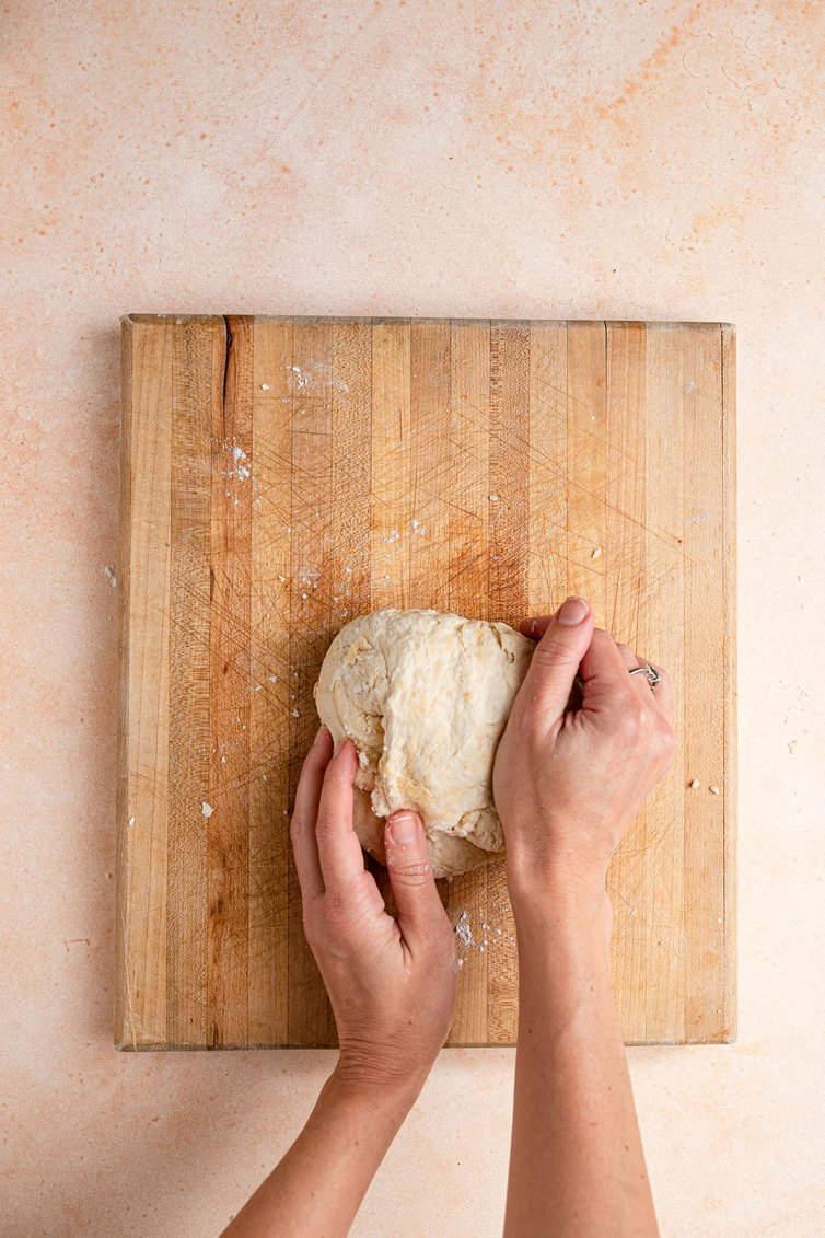 Duas mãos amassando a massa em uma placa de madeira.