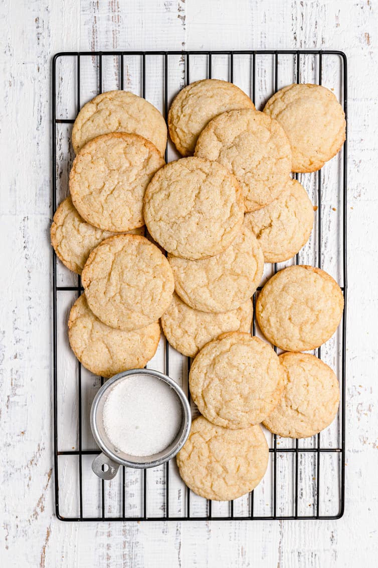 Sugar cookies on a wire rack with a bowl of sugar.