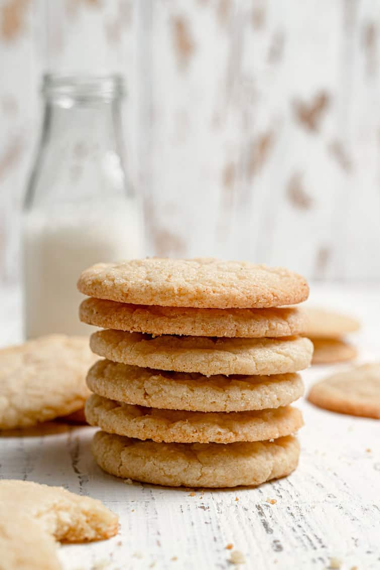 A stack of sugar cookies with a bottle of milk in the background.