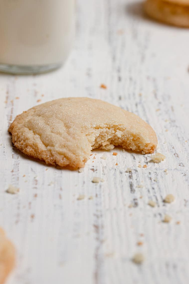 A single sugar cookie with a bite taken out of it.