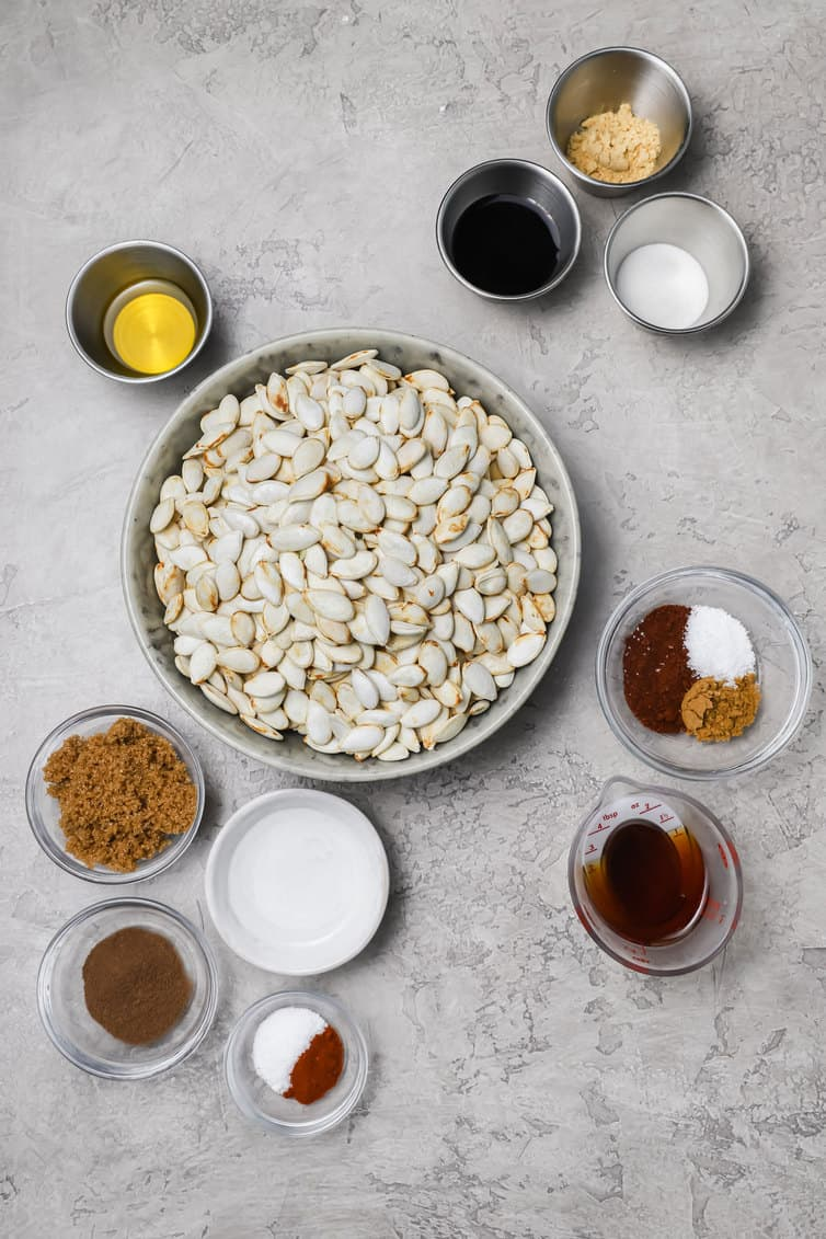 Ingredients for roasting pumpkin seeds prepped in bowls on a counter.