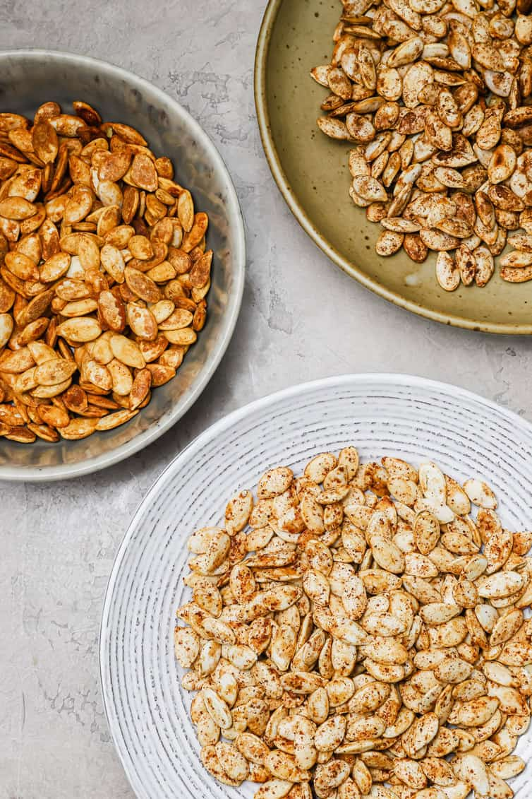Three bowls of roasted pumpkin seeds with different spice blends.