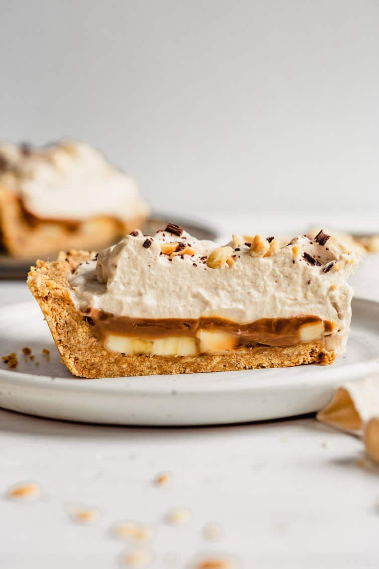 A slice of banoffee pie on a white plate, view from the side.