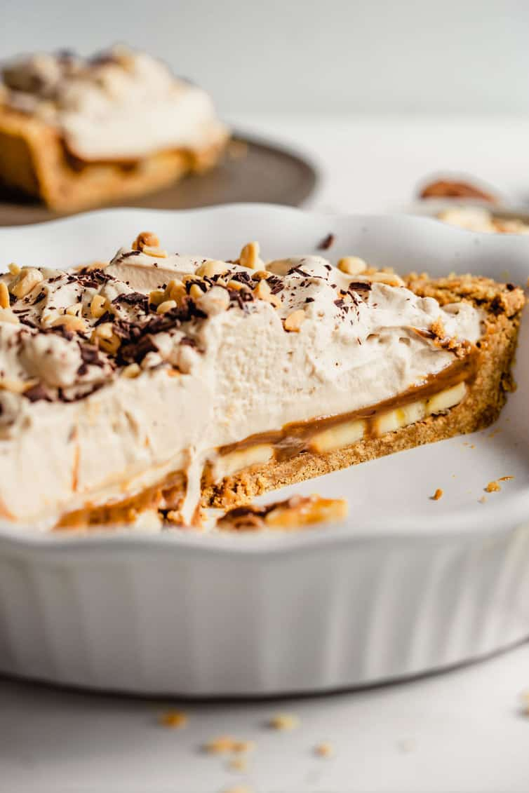 Half of banoffee pie in a pie plate.