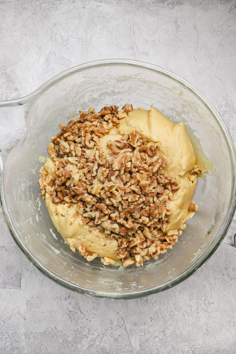 Biscotti dough in a glass bowl with chopped walnuts.