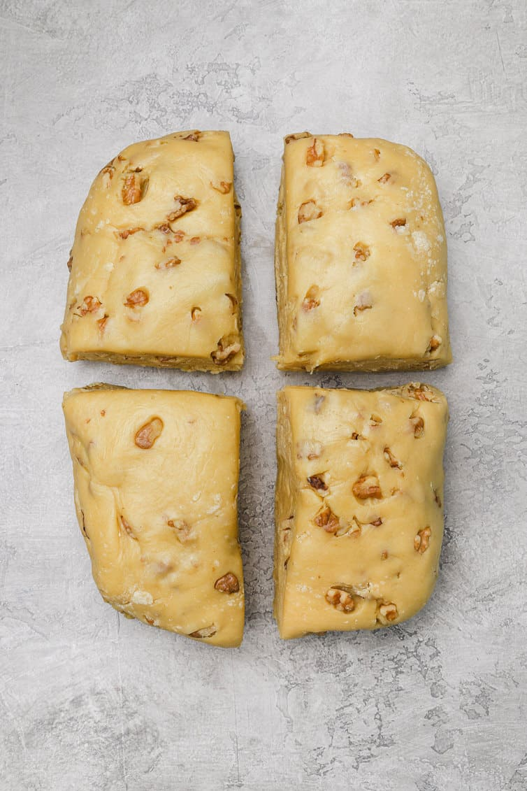 Biscotti dough divided into four pieces.