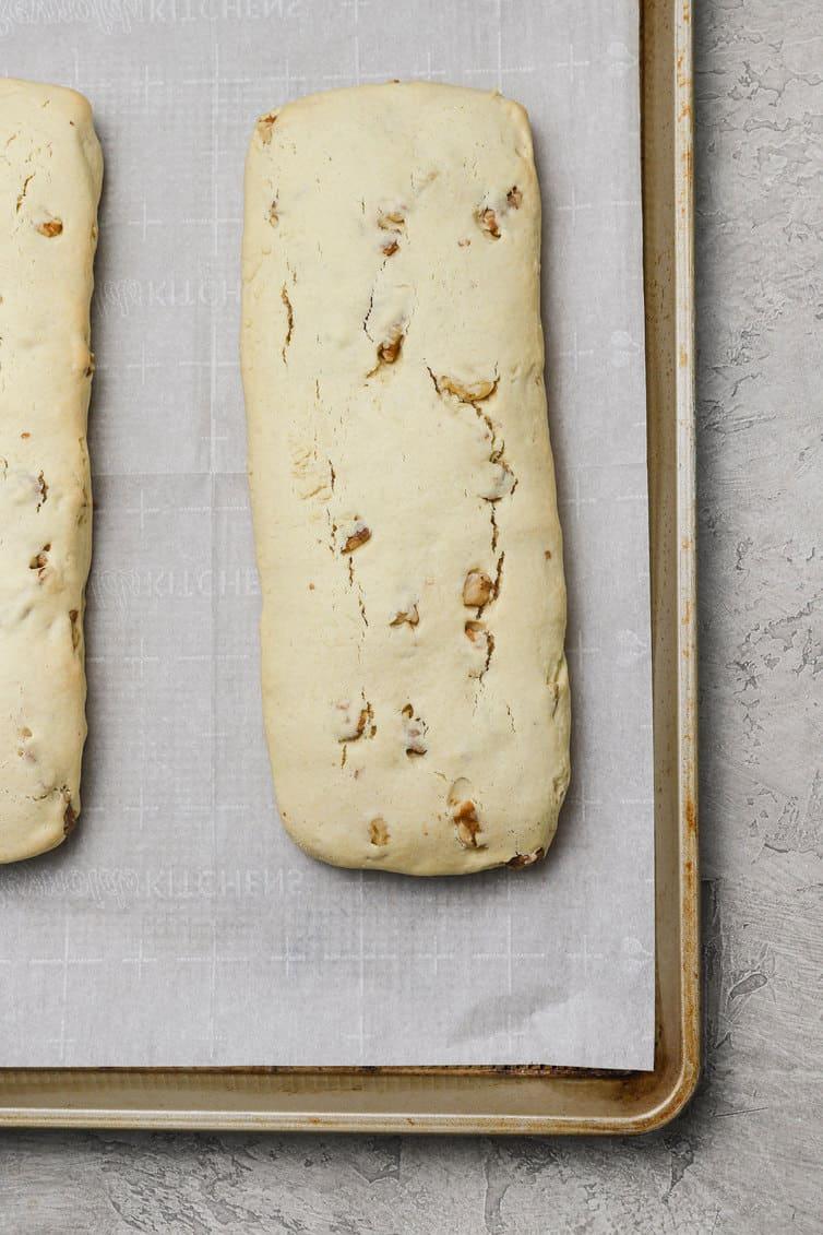Logs of biscotti baked on baking sheet.