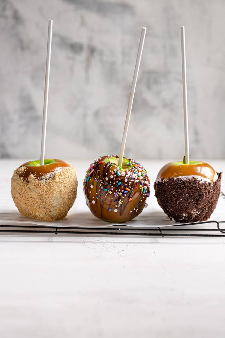 Three caramel apples in a row with different garnishes on them.