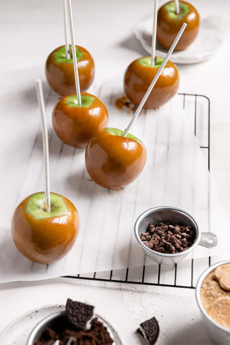 Caramel-coated apples on parchment paper on a wire rack.