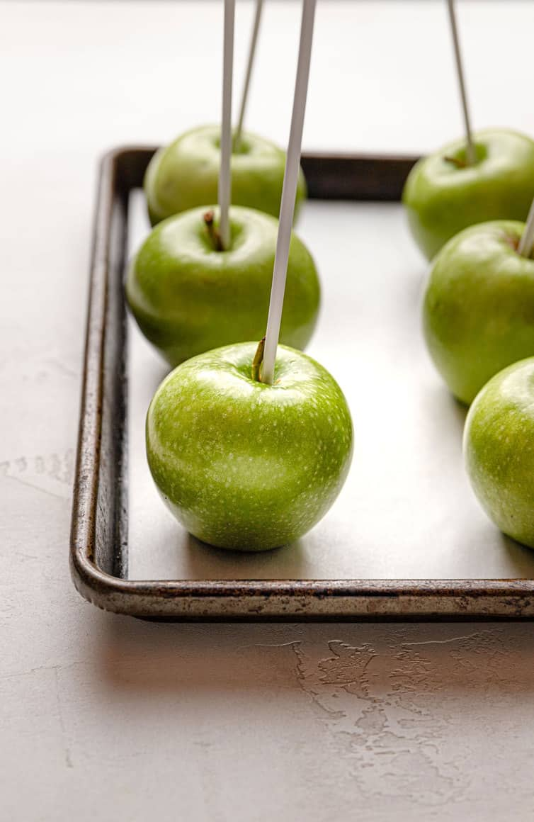 Granny Smith apples with lollipop sitcks inserted in center on a baking sheet.