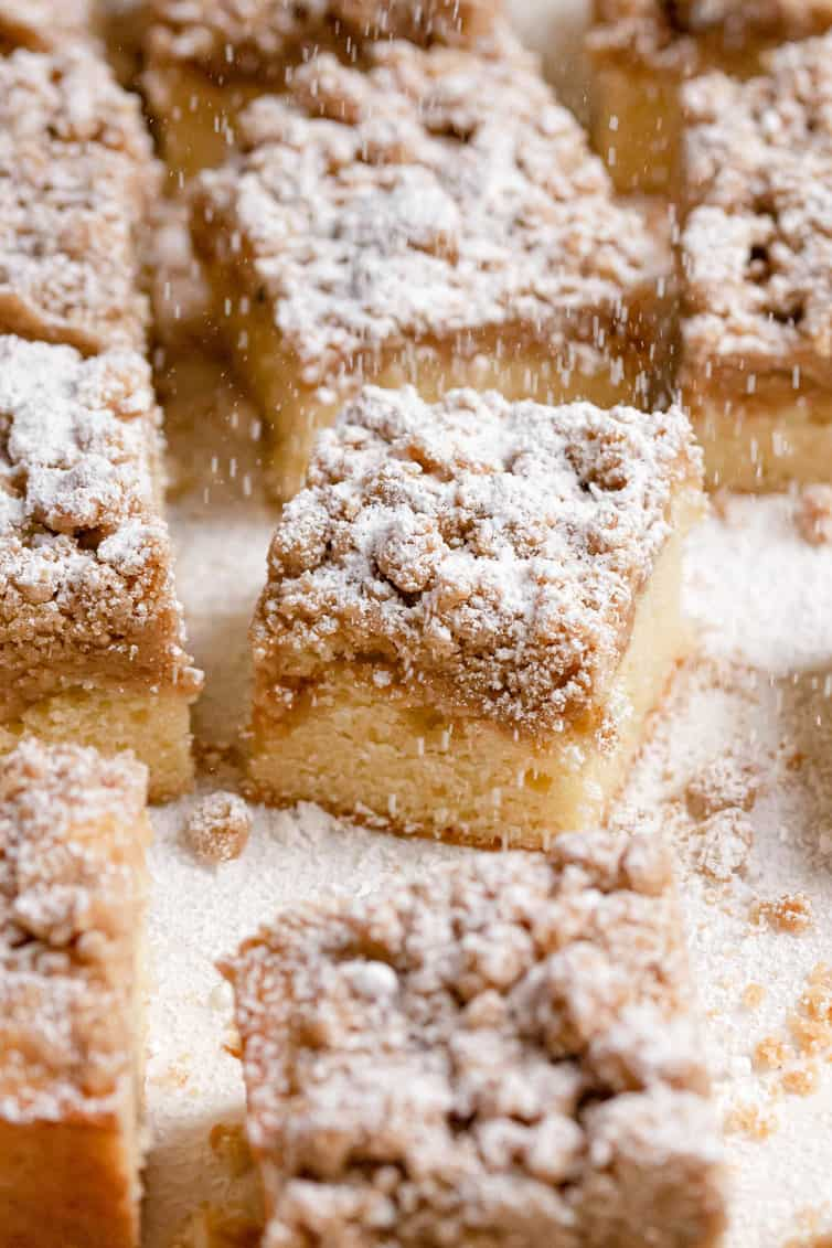 Crumb cake squares being sprinkled with powdered sugar.