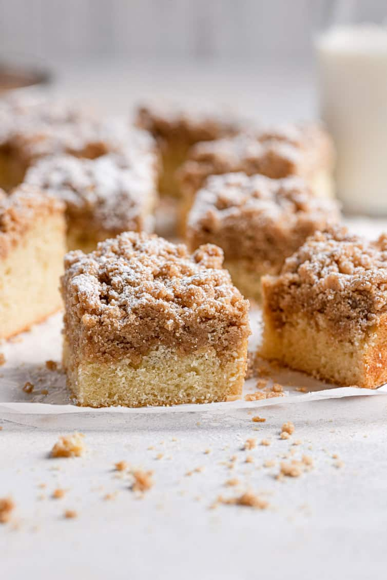 Squares of crumb cake on a surface with glass of milk in background.