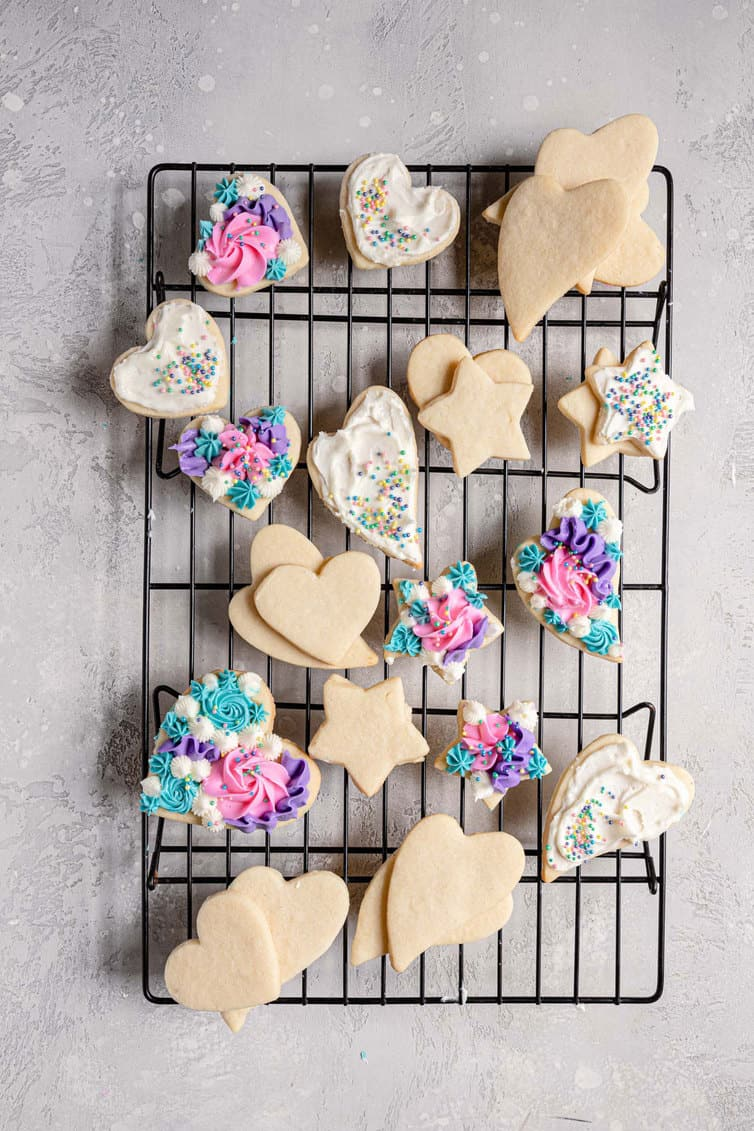 Plain and frosted sugar cookies on a cooling rack.