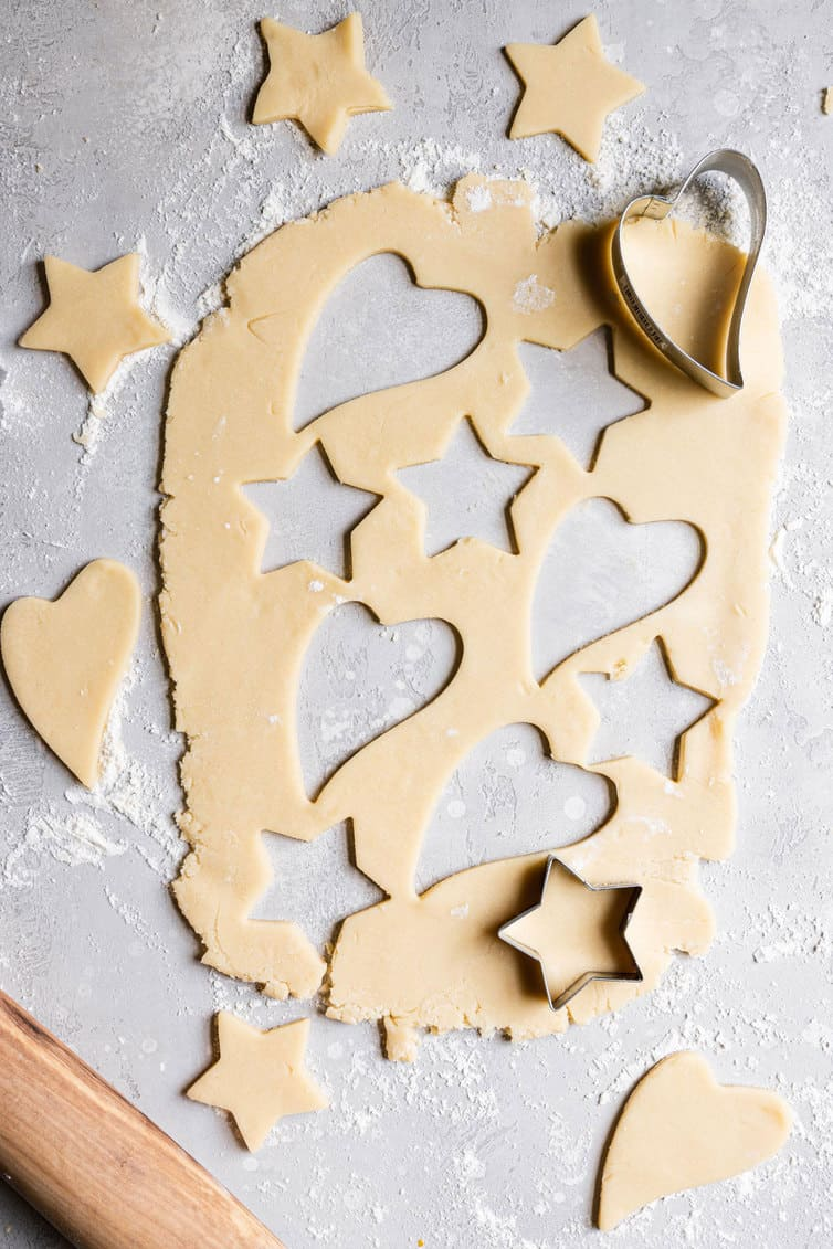 Sugar cookie dough rolled out with hearts and stars cut out.