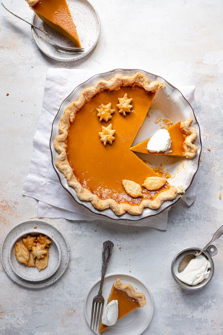 Overhead photo of pumpkin pie with sliced cut out and whipped cream on top.