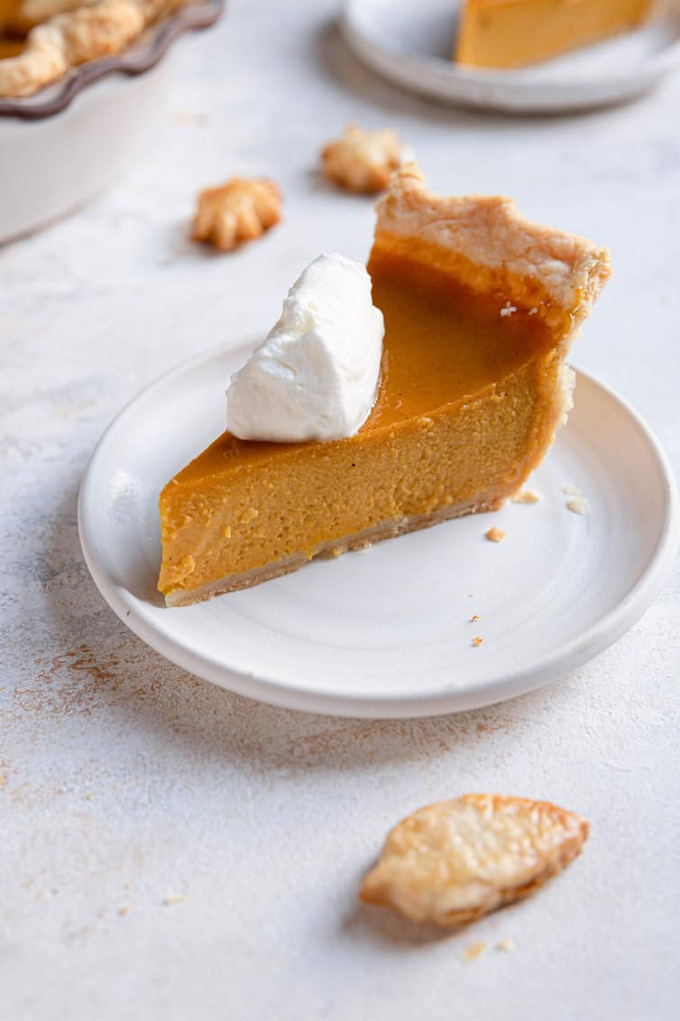 Slice of pumpkin pie on a plate with whipped cream on top.