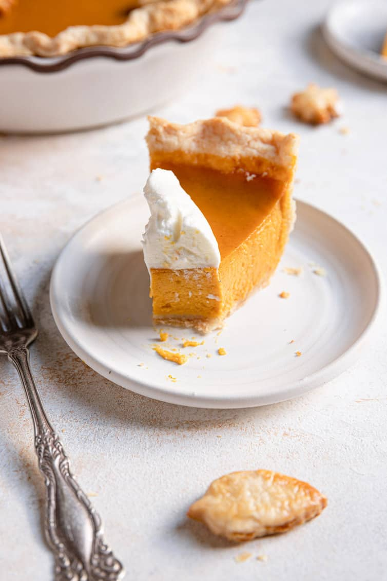 A slice of pumpkin pie with whipped cream and a forkful taken out of it.