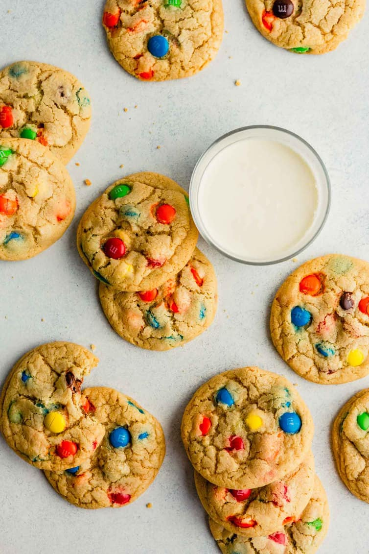 An overhead photo of M&M cookies on counter with a glass of milk.