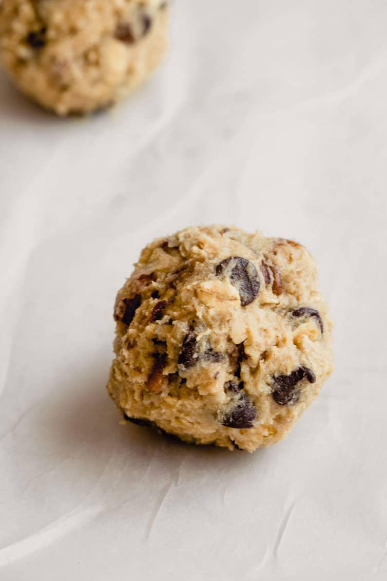Balls of cowboy cookie dough on parchment paper.