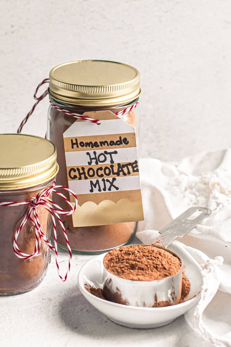 Homemade hot chocolate mix in jars and a scoop of it on a plate.