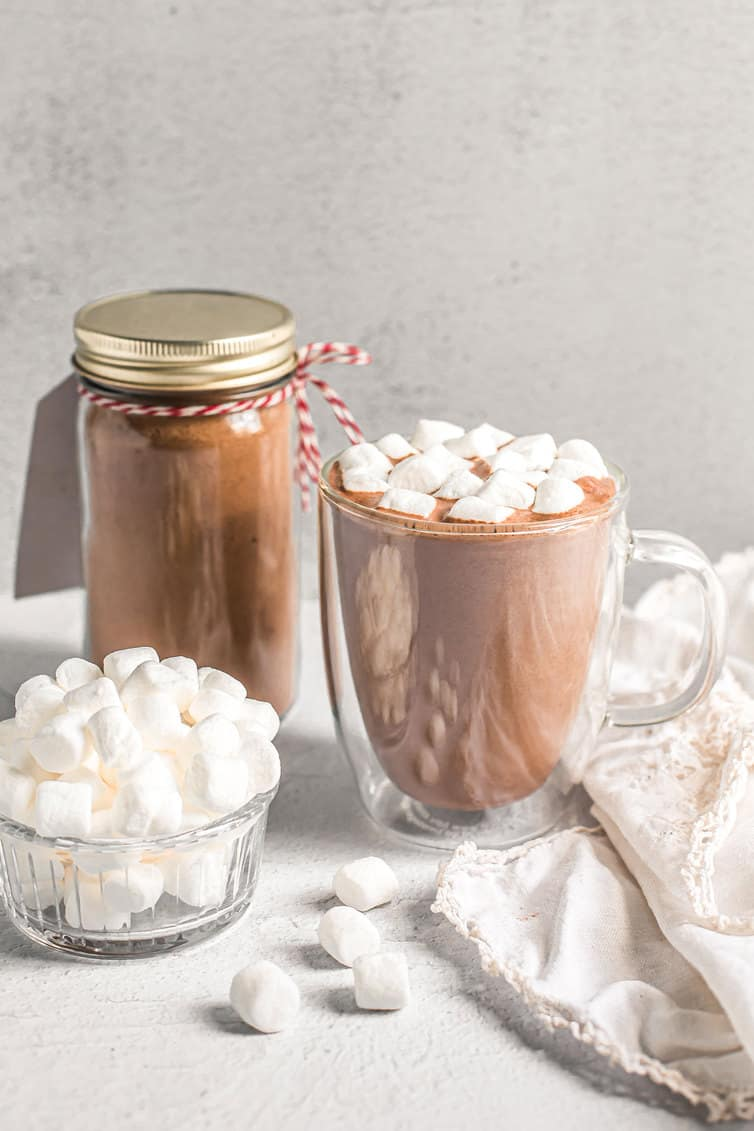 Cup of hot chocolate and mini marshmallows with mix in background.