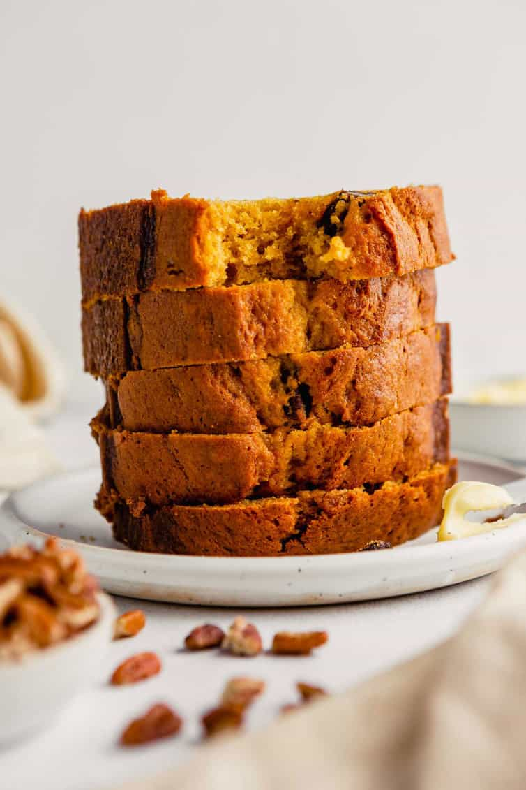 Slices of pumpkin bread stacked on a plate.