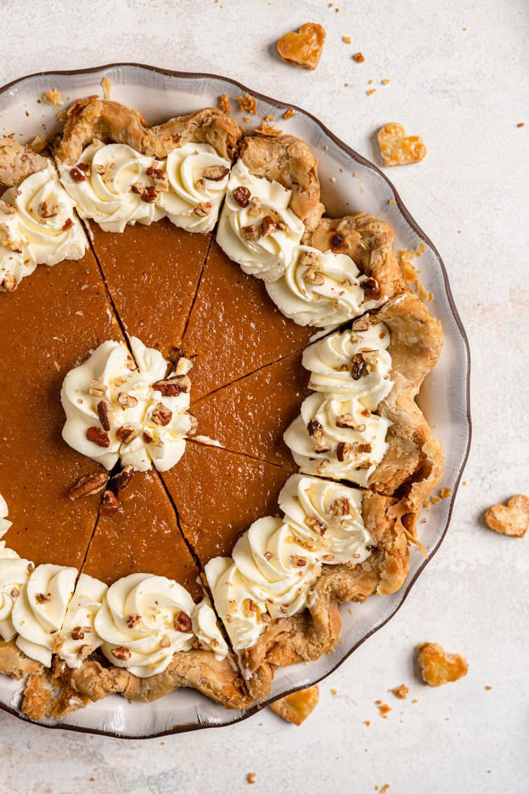 Overhead photo of sweet potato pie cut into slices with whipped cream and crushed pecans.