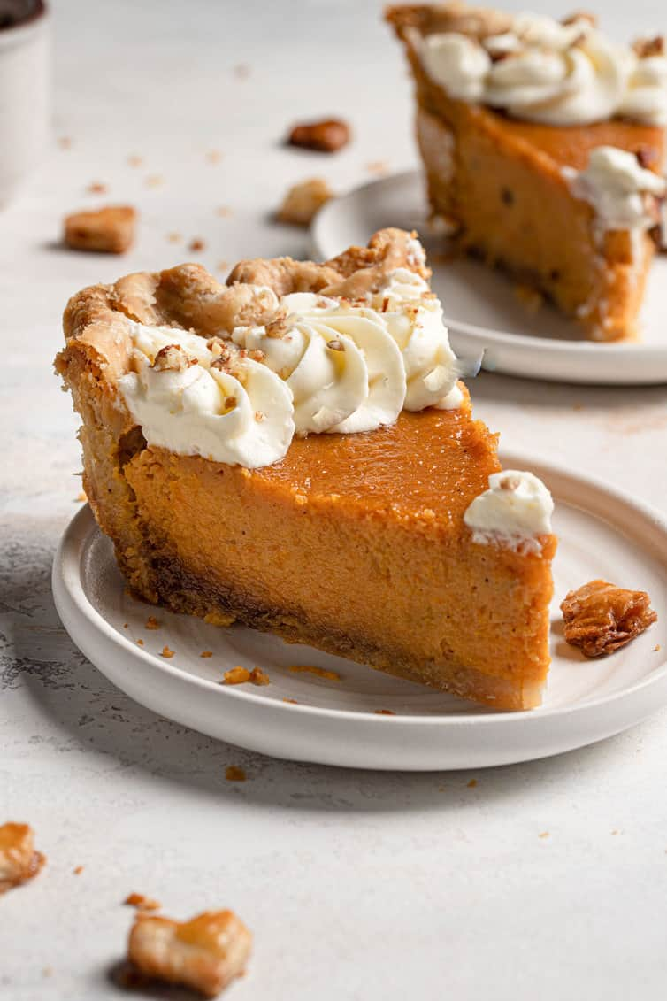 A slice of sweet potato pie with whipped cream and crushed pecans.