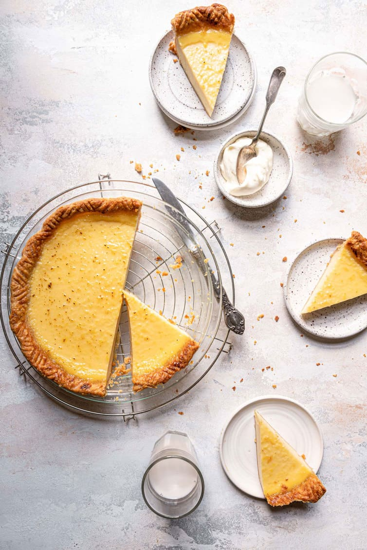 Overhead photo of buttermilk pie sliced with pieces plated.