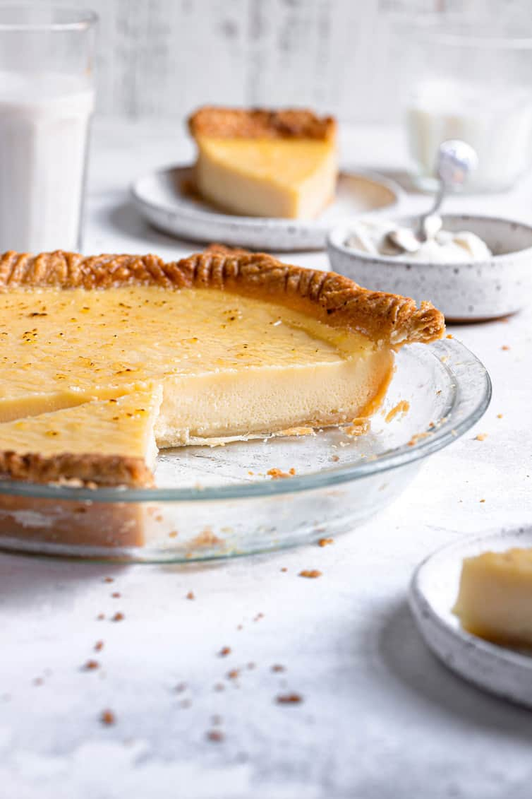 Buttermilk pie in glass pie plate with one third missing.
