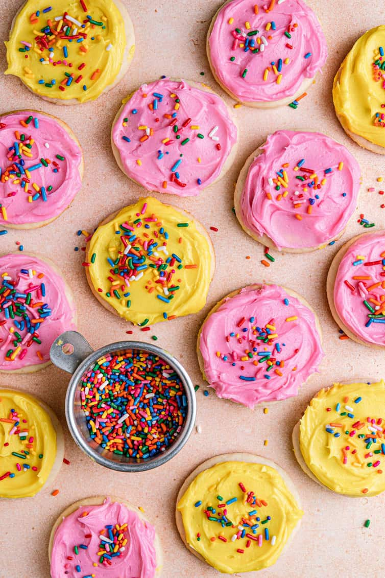 Pink and yellow frosted Lofthouse Cookies with a bowl of rainbow sprinkles.