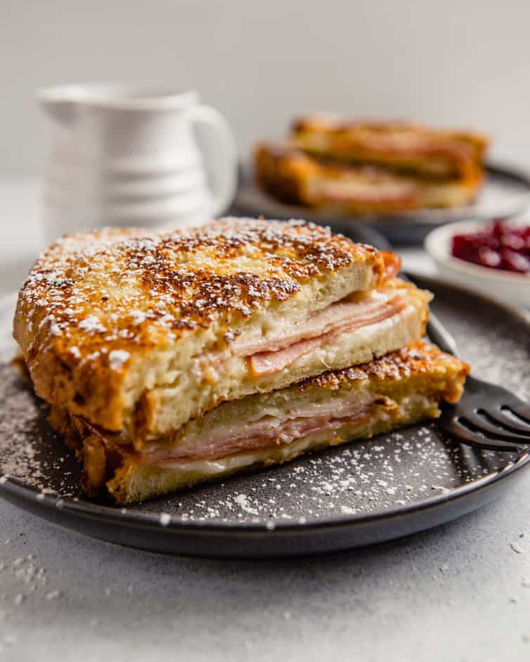 Monte Cristo sandwich cut in half and stacked, dusted with powdered sugar.