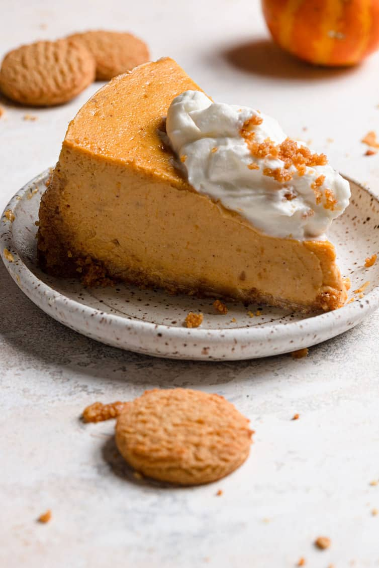 Slice of pumpkin cheesecake on plate topped with whipped cream.