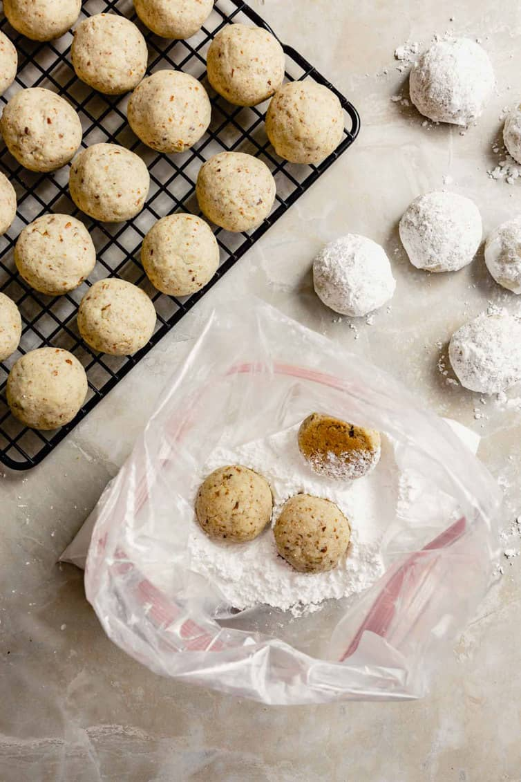 Rolling snowball cookies in powdered sugar.