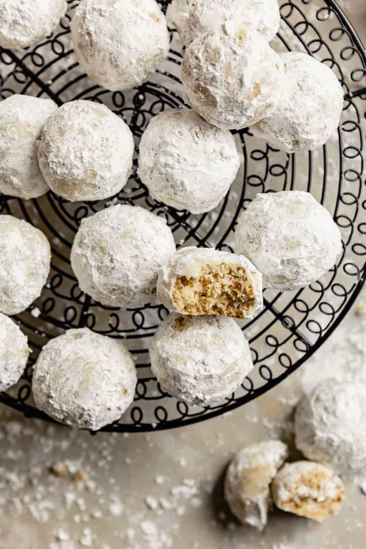 Snowball cookies on wire rack with one half eaten.
