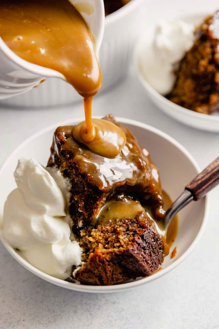 Pouring toffee sauce on sticky toffee pudding.