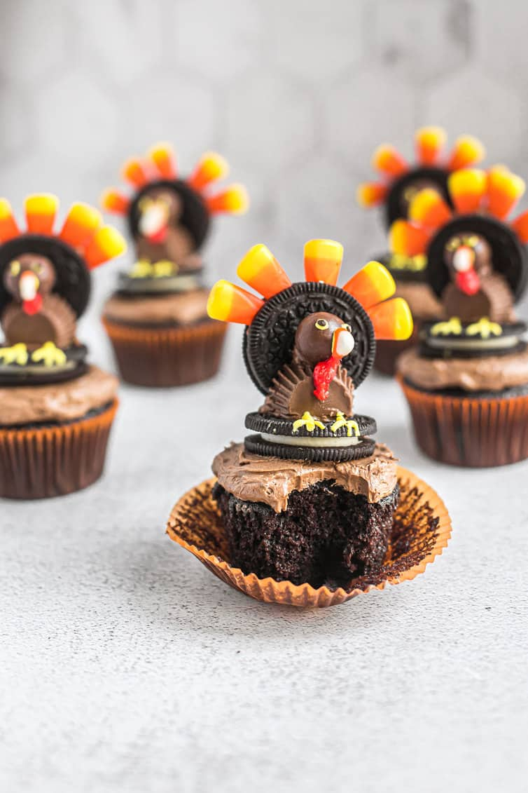 A bite taken out of chocolate cupcake with candy turkey cupcake topper.