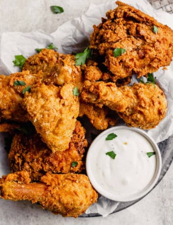 A silver plate with parchment paper topped with crispy fried chicken pieces with a small cup of ranch dressing.