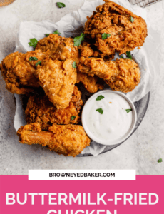 A silver plate with buttermilk fried chicken and a small bowl of ranch with a pink rectangle at the bottom and the words Buttermilk-Fried Chicken in white.