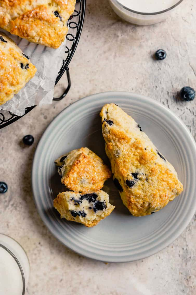 A light grey plate with two buttermilk scones on a counter with a few fresh blueberries.