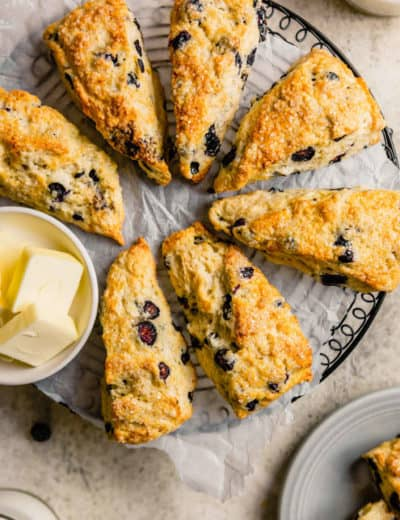 A circular cooling rack with seven buttermilk scones and a small bowl with fresh sliced butter.