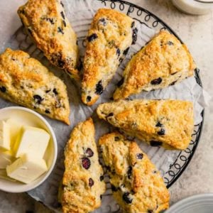 A circle of fresh buttermilk scones with blueberries on a black cooling rack covered in parchment paper with a small bowl of fresh sliced butter on the left side of the circle.